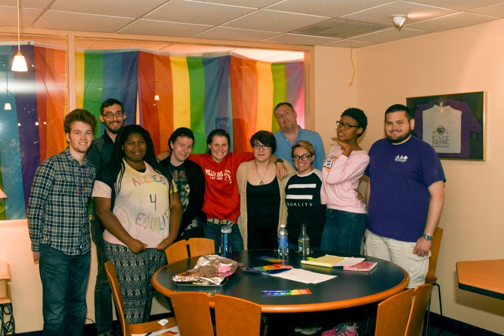 A collection of workers from the LGBT office pose with students who attended a round table discussion on what it means to come out.