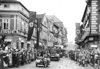 Einmarsch in das Sudetenland. Motorisierte deutsche Truppen in Saaz. German mechanized troops enter Saaz. The streets are decorated with swastika flags and banners. 9.10.1938 14.30 Uhr. Saaz. Sudetenland