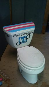 """Toilet painted with the trans flag, a bathroom sign, handcuffs and """"flush discrimination."""" Photo and art by MJ Eckhouse"""