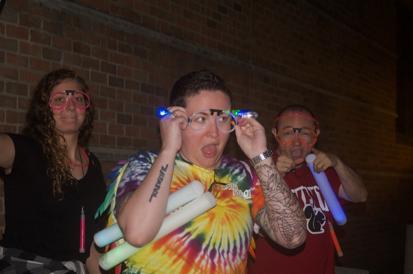 Volunteers pose with glow sticks and jewelry as That Gay 5K draws to a close.