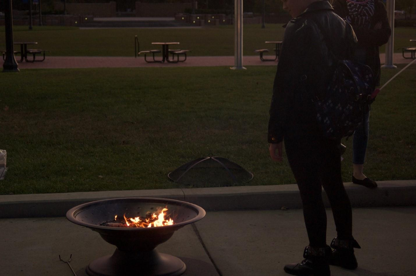 Cory Richards stands next to a fire on Risman Plaza during Take Back the Night. The event was put together by Sexual and Relationship Violence Support Services at Kent State.