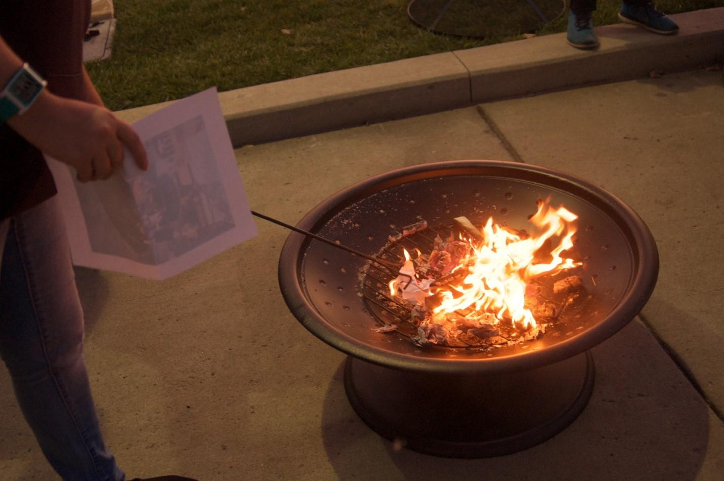 A woman burns photos of a man who sexually assaulted her during Take Back the Night.