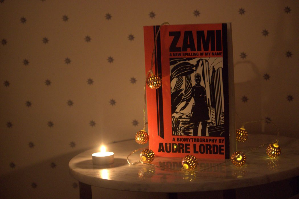 "Audre Lorde's book ""Zami: A New Spelling of my Name"" sits on a table lit with fairy lights and a candle."