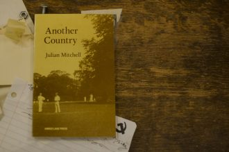 """""""Another Country"""" sits on a wood table with scribbled notes beneath."""