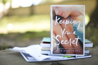 "Julie Anne Peters' novel ""Keeping You a Secret"" sits upright in front of a stack of notebooks and papers on a sunny day."