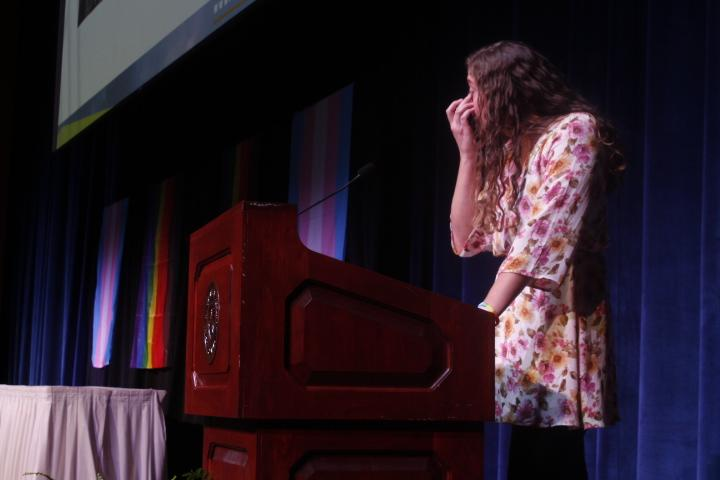 Student keynote speaker Bridget Mazzola tears up while discussing her struggles with alcoholism and accepting her sexuality. Mazzola credited her intern work with the LGBTQ Student Center for helping her to realize and accept her identity as a lesbian. Photo by Regan Schell.