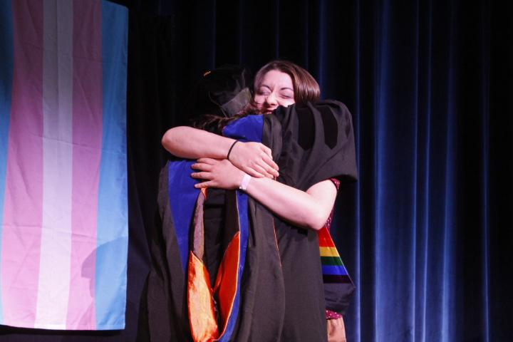 Psychology major Nicole Fogwell embraces Dr. Molly Merryman after receiving her rainbow stole. The stoles are meant to be worn at Kent's May graduation ceremony. Photo by Regan Schell.