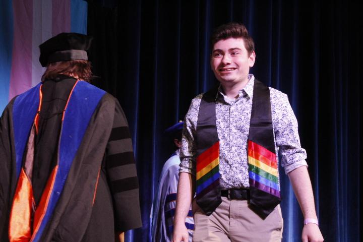 Ryan Pasquino smiles wide after taking his stole. Pasquino thanked his friends, including someone he'd met in line a few minutes before. Photo by Regan Schell.