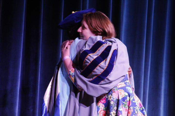 Reita Silvis hugs Dr. Alfreda Brown after delivering a tearful speech to her partner in the crowd. Silvas thanked her partner for standing by her while she underwent chemotherapy for a brain tumor while pursuing two Master's degrees. Photo by Regan Schell.