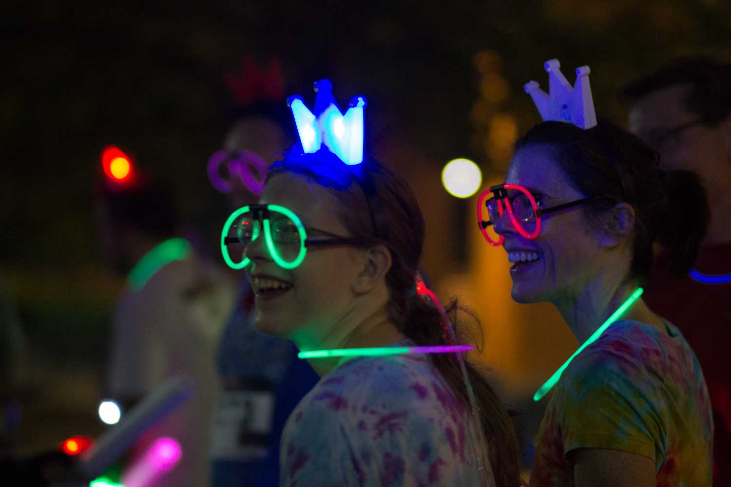 (Left to Right): Nora Vesley and Vanessa Vesley smile and cheer on the other race attendants during the Rainbow Run outside of Kent State's Student Center on Friday, Sept. 21, 2018. The theme for this year's 5k was a glow-up color run. Attendants were given glow-in-the-dark objects to guide them through the campus course. Photo by Sophia Adornetto.