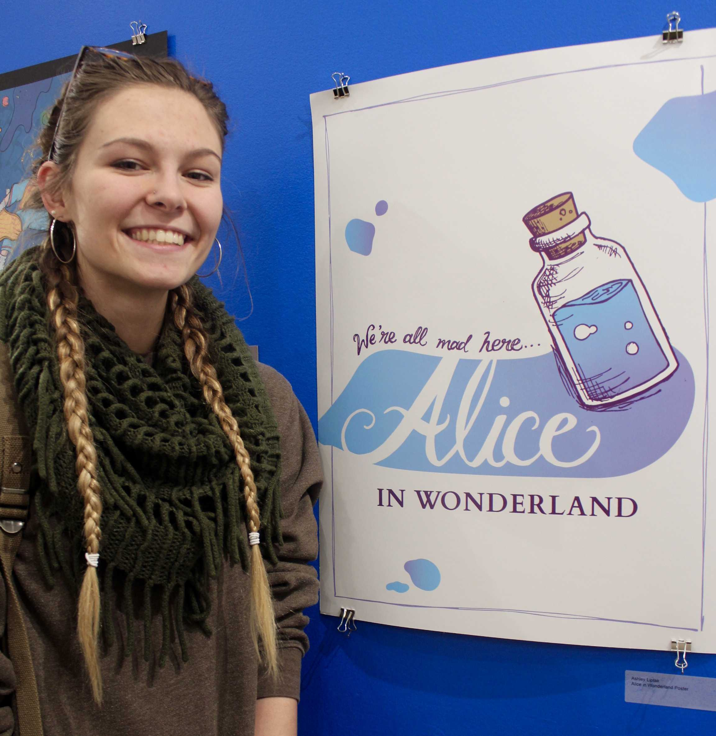 """Ashley Liptak presents her """"Alice in Wonderland Poster."""" Ashley was excited to show off her work to the university, as she takes great pride in what she designed. The inspiration came from the movie itself as she wanted to show the design in a different, artistic way. Photo by Ashley Miller."""